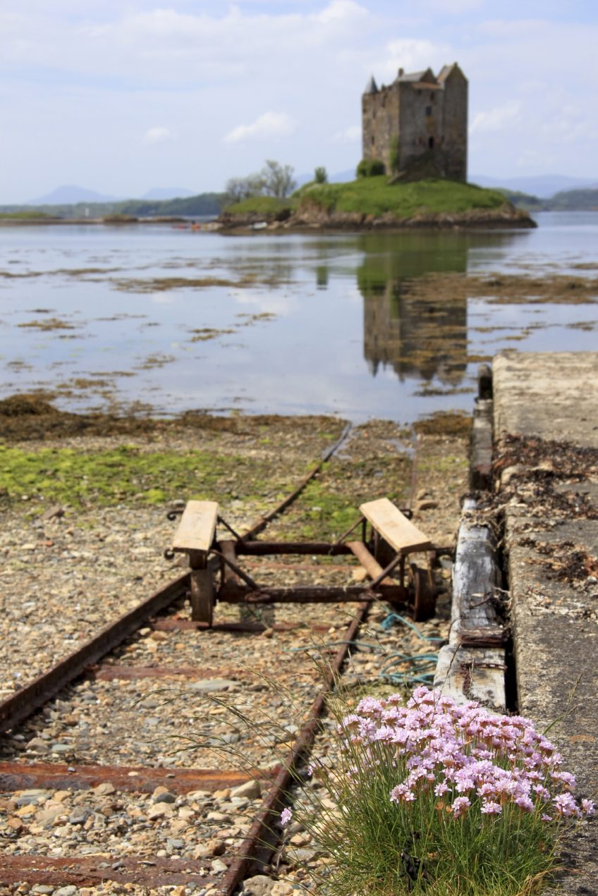 old overgrown jetty for medieval castle stalker on small island in loch linnhe argyll in the scottish highlands